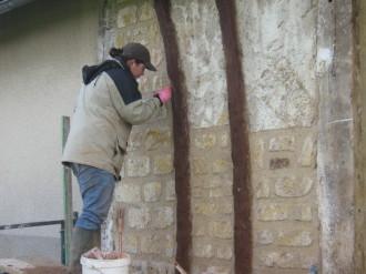 stagiaire exécutant une sculpture de poutre en béton et de fausses pierres